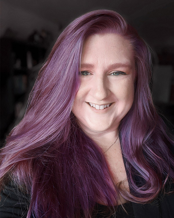 Portrait of me. I am white with blue eyes and purple hair. I'm wearing a black blazer. The background is dark and blurry.